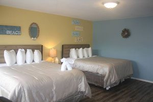 Bedroom with two beds, one blue wall, one yellow wall