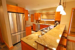 Kitchen with hanging lights and granite counter tops