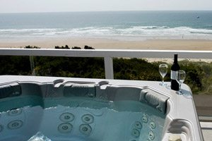 Hot tub with wine bottle and glasses on the side, set up on balcony next to the beach