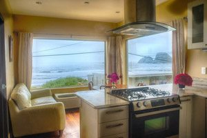 Kitchen and living room with windows looking out over the beach