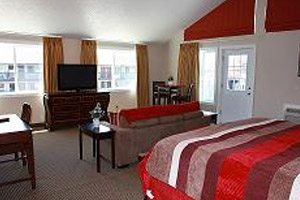 Hotel room with bed, living room and television