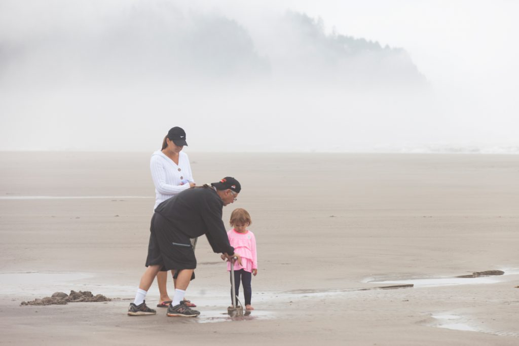 Man, woman and child stand on beach in fog