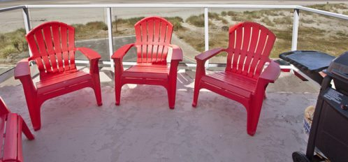 Red chairs in a circle next to a grill on a balcony over the beach