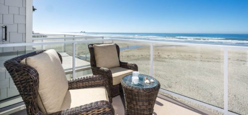 Balcony with two wicker chairs and a table, view of the beach