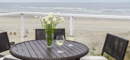 Chairs and table on porch overlooking the beach