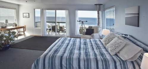 Small bedroom with blue bedspread and telescope next to window that looks out on the beach