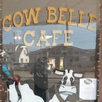 Cow Belle Cafe sign with cow drawings window of store