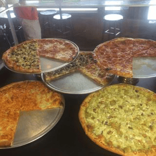 Five pizzas on serving plates