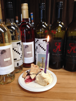 Paper plate with pie and ice cream, surrounded by full bottles of wine