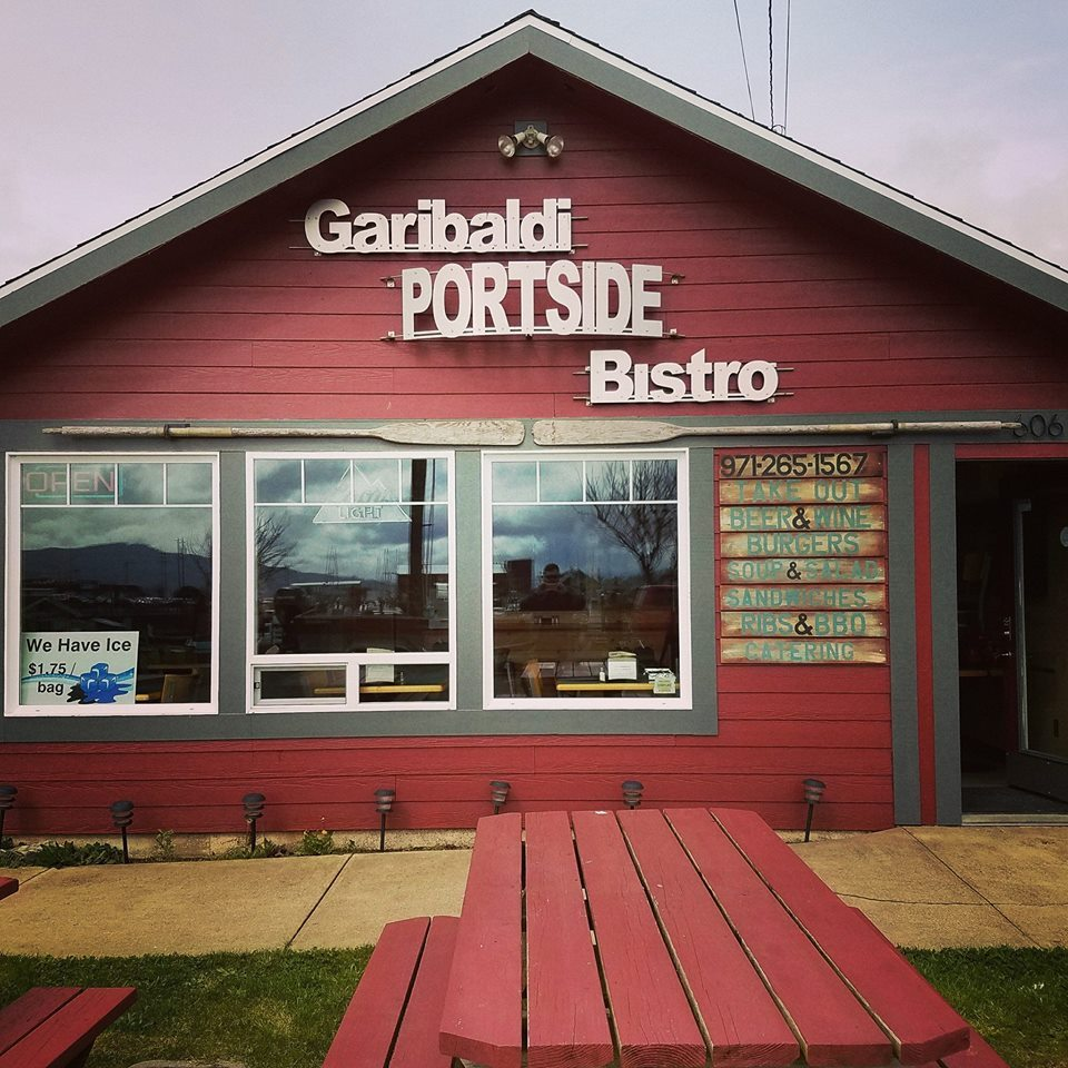 Exterior of Garibaldi Portside Bistro, a small red building with picnic tables in front