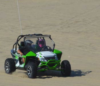 Two people sit in an ATV driving across sand dunes